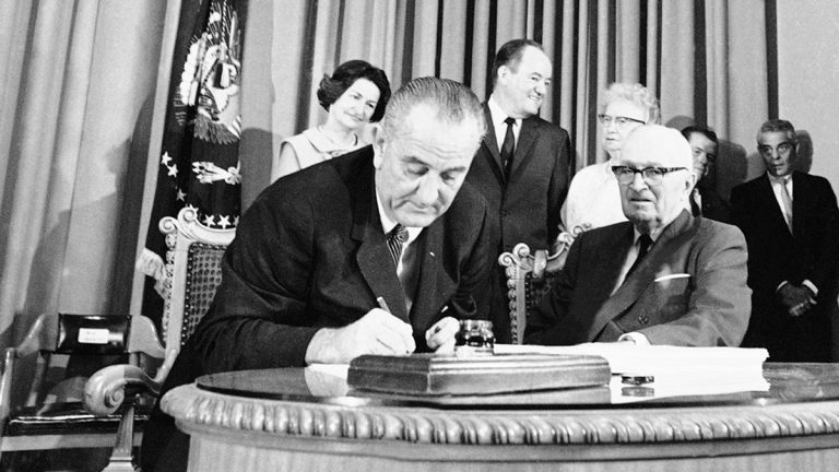 In this July 30, 1965, file photo President Lyndon B. Johnson, (left), with former Pres. Harry S. Truman at his side, uses the last of many pens to complete the signing of the Medicare Bill into law at ceremonies at the Truman Library in Independence, Missouri. John signed Medicare for people age 65 and older and Medicaid for the poor into law. His legendary arm-twisting and a Congress dominated by his fellow Democrats succeeded in creating the kind of landmark health care programs that eluded his predecessors. At rear from left are Lady Bird Johnson, Vice President Hubert Humphrey, and former first lady Bess Truman. (AP Photo, File)