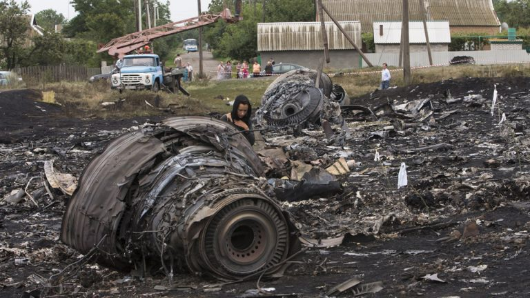 A woman walks at the site of a crashed Malaysia Airlines passenger plane near the village of Rozsypne, eastern Ukraine Friday, July 18, 2014. Rescue workers, policemen and even off-duty coal miners were combing a sprawling area in eastern Ukraine near the Russian border where the Malaysian plane ended up in burning pieces Thursday, killing all 298 aboard. (Dmitry Lovetsky/AP Photo)