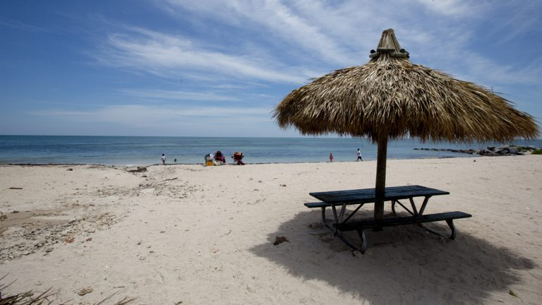 In this April 21, 2014 photo, people walk along one of the beaches in Key Biscayne, Fla. While there is a wide open beach now, many officials fear that in years to come, rising sea levels may destroy the open area. (J. Pat Carter/AP Photo)