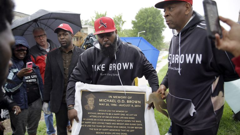 Michael Brown Sr. holds up a plaque honoring his son, Michael Brown, to show volunteers as they remove items left at a makeshift memorial last month in Ferguson, Missouri. The memorial that has marked the place where Brown was fatally shot by a police officer in August has been removed and will be replaced with the permanent plaque. (Jeff Roberson/AP Photo)