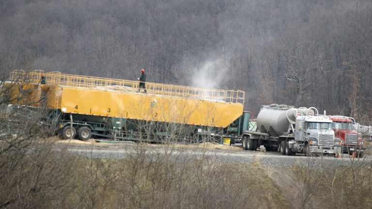 A worker walks on top of a container of chemicals used in the making of a brine water that is then pumped below the surface in a hydraulic fracturing process to release natural gas from shale deposits at a gas well site in Zelienople, Pa. A new fee on gas drilling has generated millions of dollars more in revenue than first projected, but other major gas-producing states tax the industry at higher rates. (Keith Srakocic/AP Photo, file)