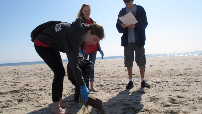 In this April 2012 photo, three teens participate in beach sweeps sponsored by the Clean Ocean Action environmental group, removing thousands of items that were either left behind by beachgoers, or that washed up with the tides after being discarded elsewhere. (Wayne Parry/AP Photo, file)
