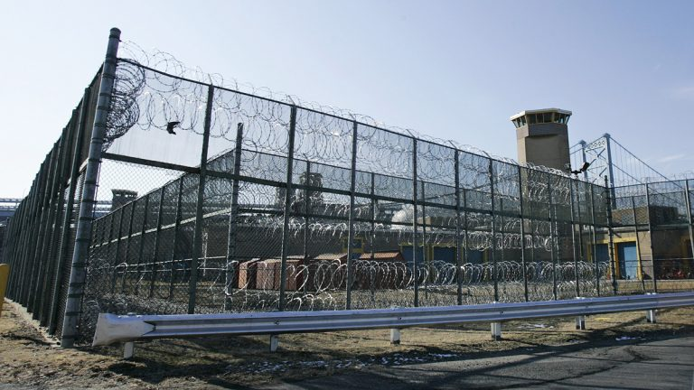 A guard tower and razor wire at New Jersey Department of Corrections Riverfront State Prison are seen in Camden, N.J., not far from the span, left, of the Benjamin Franklin bridge that crosses the Delaware River to Philadelphia.