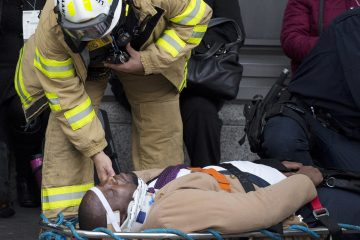 An injured passenger is assisted by an EMS worker as he lies on a gurney outside Atlantic Terminal after a Long Island Rail Road incident