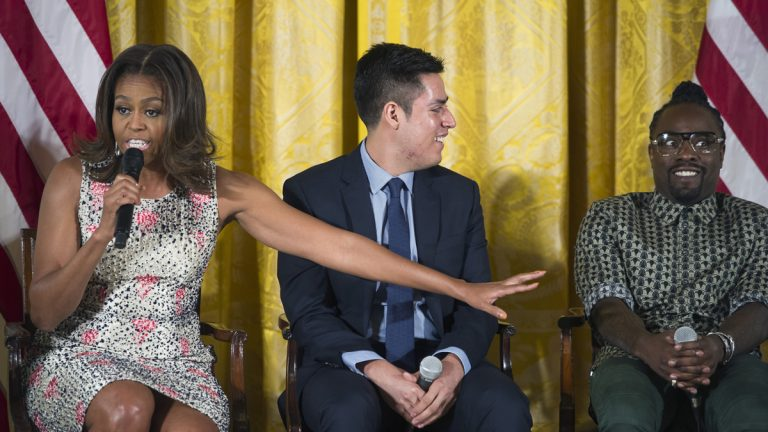 First lady Michelle Obama gestures to musical artist Wale, (right), as Manuel Contreras, (center), looks on, during an East Room event to welcome more than 130 college-bound students from across the county to participate in the 2015 Beating the Odds Summit at the White House in Washington, Thursday, July 23, 2015. The summit is part of the first lady's Reach Higher initiative. (Cliff Owen/AP Photo)