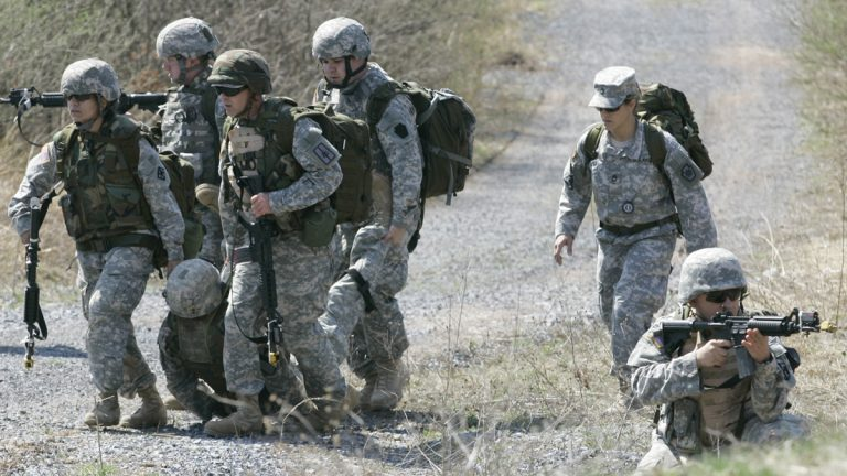 A member of the Pennsylvania National Guard takes up a security position while others remove an injured man during a battle simulation exercise at Fort Indiantown Gap in Annville, Pa. (Carolyn Kaster/AP Photo, file)