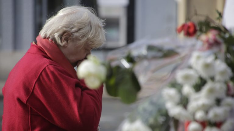 A woman pays her respects at a makeshift memorial next to the Bataclan concert hall in Paris Wednesday. (Amr Nabil/AP Photo)