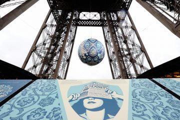 American street artist Shepard Fairey, aka Obey's latest piece, 'Earth Crisis', a giant sphere themed on environment hangs between the first and second floor of the Eiffel Tower in Paris, Friday, Nov. 20, 2015. Obey's art piece which weighs 2,3 tons will be displayed until Nov. 26 as Paris will be hosting the climate change conference from Nov. 30-Dec. 11, 2015. (Binta Epelly/AP Photo)