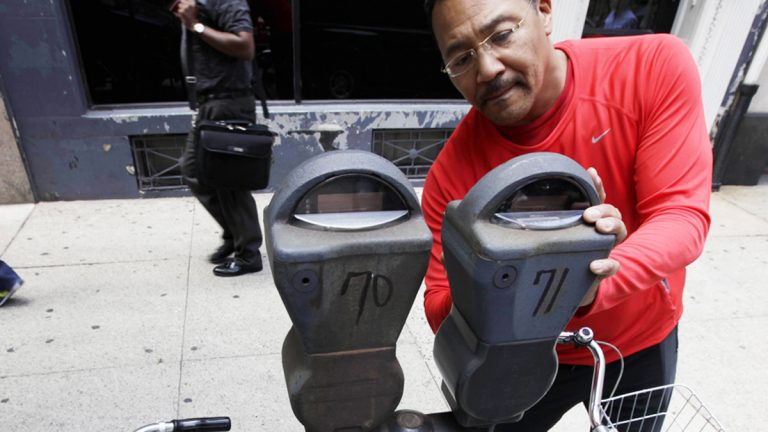 A motorist feeds a parking meter in Philadelphia in this 2009 photo. The city has since installed multi-space kiosks where drivers can pay electronically, but these old vestiges still linger in some neighborhoods. The Parking Authority is now looking into a new round of high-tech parking meters. (Matt Rourke/AP Photo)