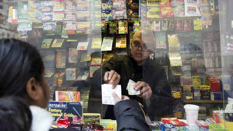 Atul Amin sells Powerball tickets at his news stand in Philadelphia in February. Revenue from jackpot games is about 23 percent below last year's level, according to the Pennsylvania Lottery director.(AP file photo)