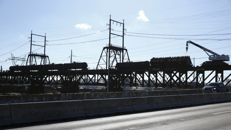 In this Jan. 24, 2014, photo, railroad crews transfer flammable crude oil from from five derailed tank cars on a bridge over the Schuylkill River, in Philadelphia.  (Matt Rourke/AP Photo, file)
