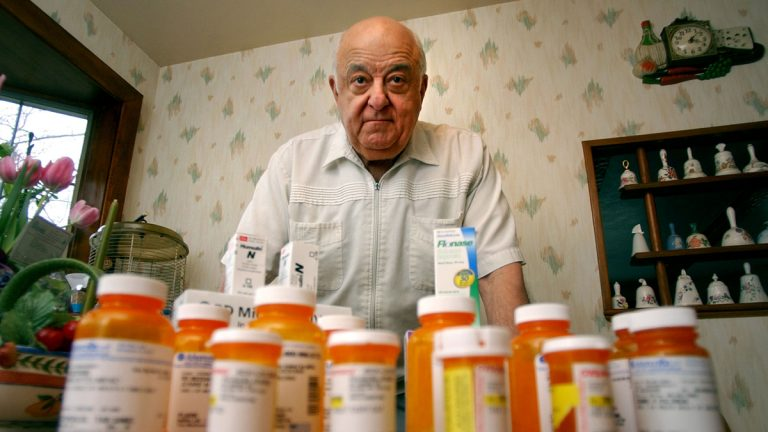 A man poses in the kitchen of his home with his wife's daily medication. (Charles Krupa/AP Photo)