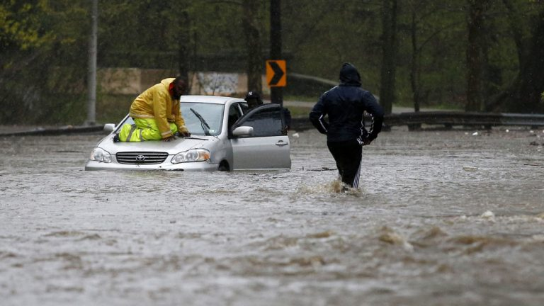 A man walks across a flooded section of the Cobbs Creek Parkway as a tow truck worker tries to free a swamped car, Wednesday, April 30, 2014, in Philadelphia. (AP Photo)
