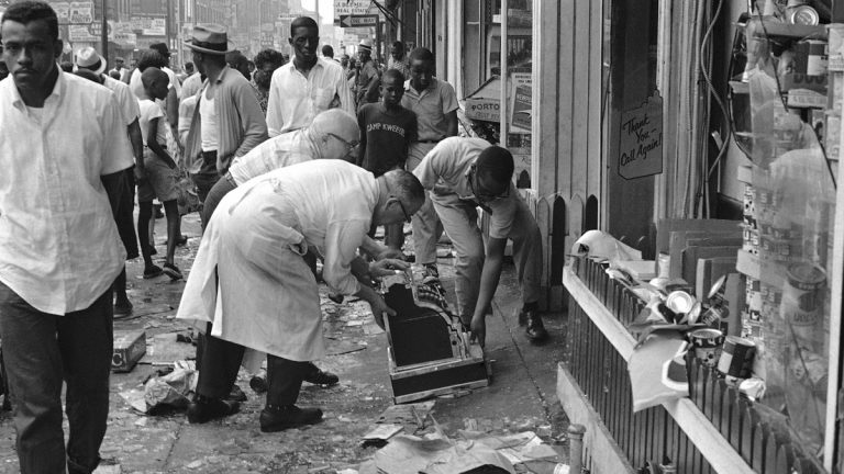 Workmen pick a cash register off the sidewalk in front of smashed store, Aug. 29, 1964, wrecked during wild night of looting and rioting in North Philadelphia. Rioting that ended in injuries to scores and widespread property damage apparently began in scuffle during a routine arrest. (John F. Urwiller/AP Photo)