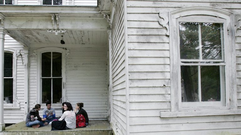 A group of high school students read poetry as they sit on the porch of an old home. (Mel Evans/AP Photo)