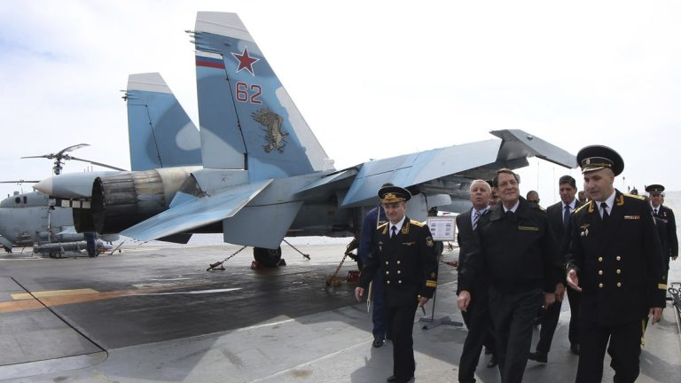 "In this handout photo released from Cyprus Information Office, President of Cyprus Nicos Anastasiades, front second from right, walks with members of the Russian aircraft carrier ""Admiral Kuznetsov"" during his tour of the vessel outside of Limassol port south of Cyprus, Friday, Feb. 28, 2014. Anastasiades said Cyprus can act as a stabilizing factor in a tumultuous region because it's uniquely positioned to offer its facilities to warships that engaged in enhancing regional peace and security. The aircraft carrier arrived in Cyprus Thursday for a three-day rest and resupply stay. (AP Photo/Press and Information Office)"