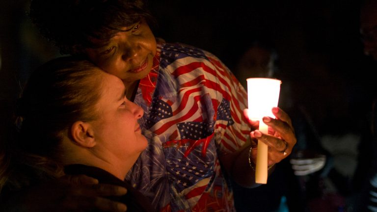 Lisa Hamons, front, a social worker for San Bernardino County, is hugged by Yolanda Richardson during a candlelight vigil for shooting victims  in San Bernardino, Calif. (Jae C. Hong/AP Photo)