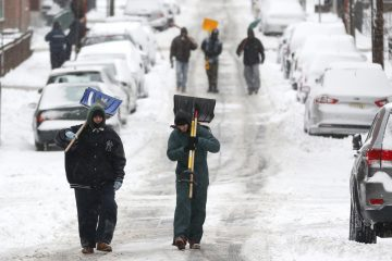 Men carry shovels as they walk on a snow covered road after an overnight snowstorm. (Julio Cortez/AP Photo)