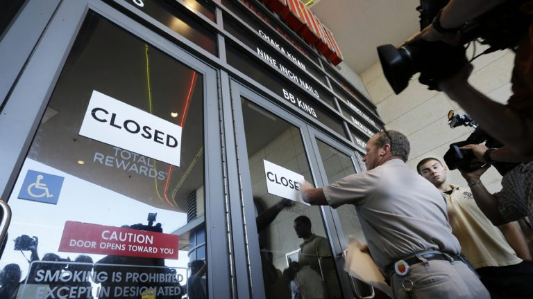 Workers put closed signs on the entrance of the Showboat Casino Hotel, Sunday, Aug. 31, 2014, in Atlantic City, N.J. The show is ending for the Showboat Casino Hotel in Atlantic City. The Mardi Gras-themed casino shut down Sunday after 27 years on the Boardwalk. (Mel Evans/AP Photo)