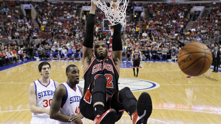 Chicago Bulls' Taj Gibson (22) hangs on the rim after dunking the ball against Philadelphia 76ers' Jarvis Varnado (40) and Byron Mullens (30) during the first half of an NBA basketball game, Wednesday, March 19, 2014, in Philadelphia. (Matt Slocum/AP Photo)
