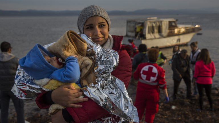 A Syrian woman holds her baby after their arrival on a small boat from the Turkish coast on the northeastern Greek island of Lesbos Monday