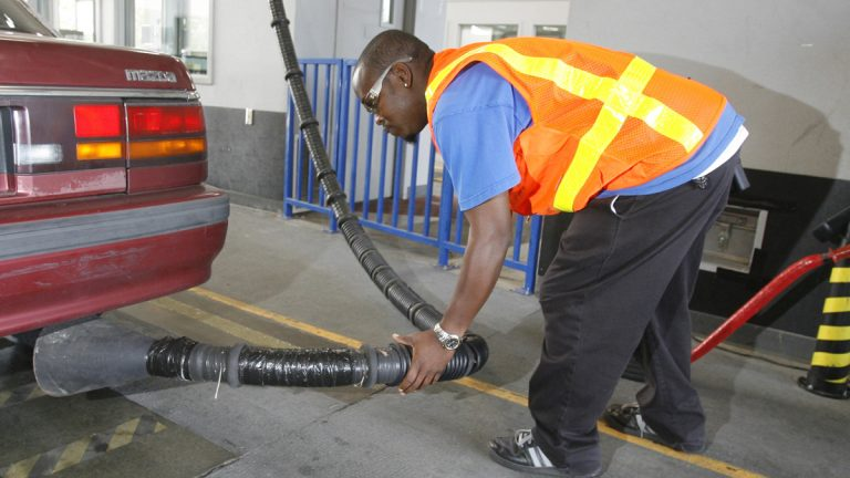 A vehicle inspector conducts a tailpipe emission test. (Rick Bowmer/AP Photo)