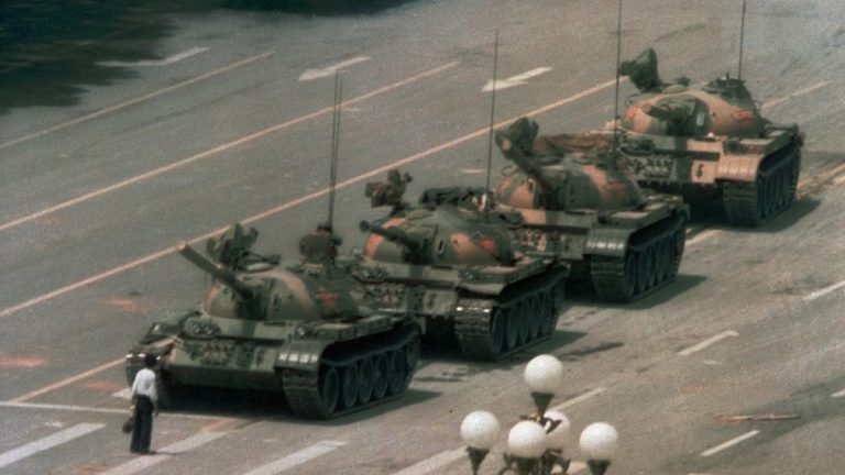 A Chinese man stands alone to block a line of tanks heading east on Beijing's Cangan Blvd. in Tiananmen Square on June 5, 1989.  The man, calling for an end to the recent violence and bloodshed against pro-democracy demonstrators, was pulled away by bystanders, and the tanks continued on their way. (Jeff Widener/AP Photo)