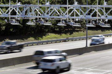 Cars pass under toll sensor gantries hanging over the Massachusetts Turnpike