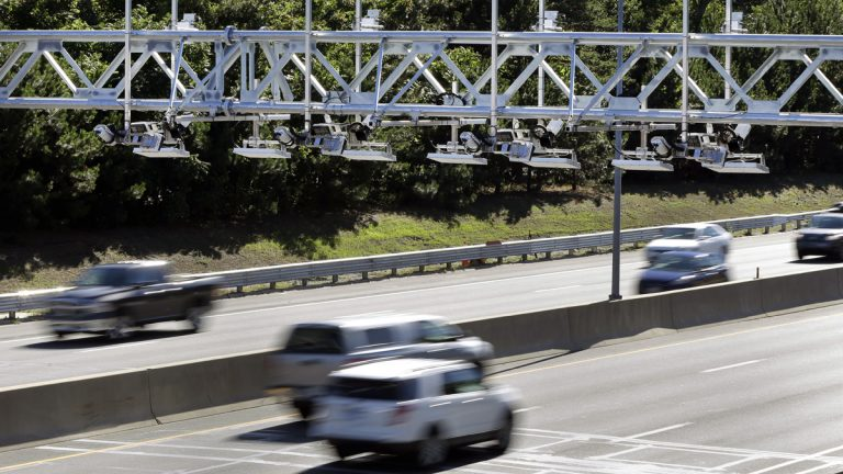 Cars pass under toll sensor gantries hanging over the Massachusetts Turnpike