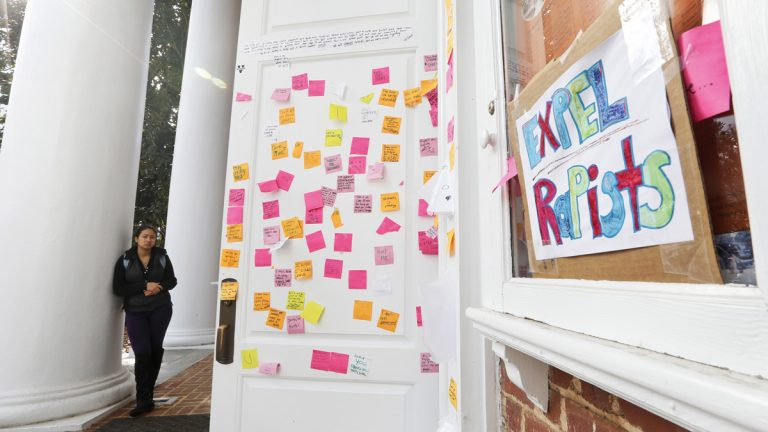 A University of Virginia student looks over postings on the door of Peabody Hall related to the Phi Kappa Psi gang rape allegations at the school in Charlottesville, Va., Monday, Nov. 24, 2014. The university has suspended activities at all campus fraternal organizations amid an investigation into a published report in which a student described being sexually assaulted by seven men in 2012 at the Phi Kappa Psi house. (Steve Helber/AP Photo)