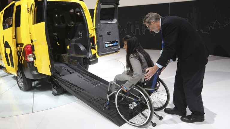 A model demonstrates the  features of a wheelchair-accessible taxi at the 2013 New York International Auto Show. (AP Photo/Mary Altaffer)