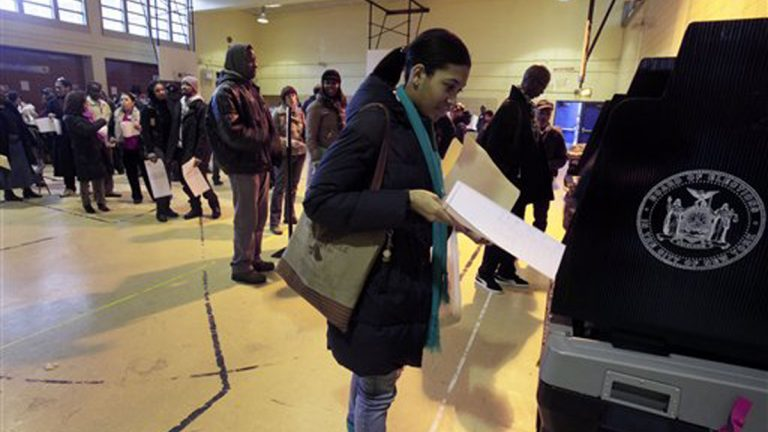 A woman scans her ballot after voting at a school (Richard Drew/AP Photo)