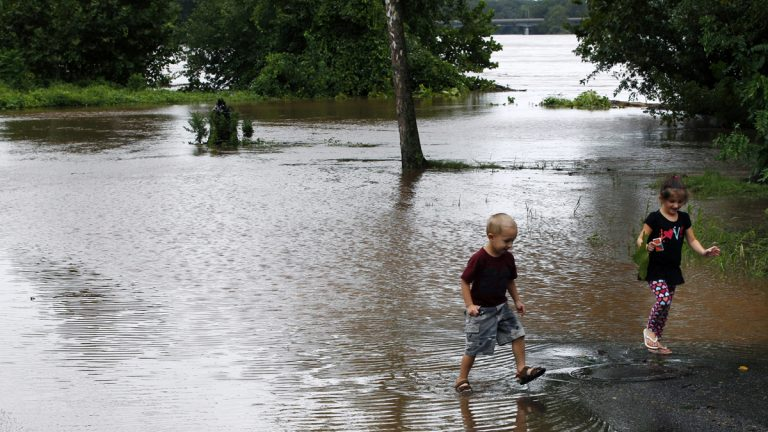 A brother and sister walk in a flooded Delaware Avenue in Yardley, Pa., in August 2011 as the Delaware River overflowed after rains from Hurricane Irene. (Mel Evans/AP Photo)