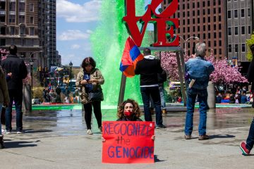Arpy Miniasian sits in silence in front of the Love Park sign and fountain. (Brad Larrison/for NewsWorks)