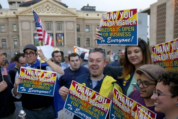 Demonstrators celebrate at the Arizona Capitol on Wednesday after learning that Arizona Gov. Jan Brewer vetoed SB1062, a bill designed to give added protection from lawsuits to people who assert their religious beliefs in refusing service to gays. (AP Photo/Ross D. Franklin)