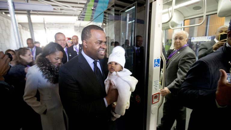 Atlanta Mayor Kasim Reed holds his six-month-old daughter Maria Kristan while boarding an Atlanta Streetcar with wife Sarah-Elizabeth, left, for its inaugural trip through downtown Atlanta in 2014. Reed says the streetcar's 2.7-mile route will connect neighbors to several tourist attractions, museums and entertainment venues. (AP Photo/David Goldman)