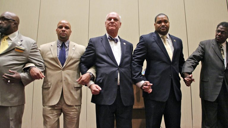 Atlantic City Mayor Don Guardian (center) holds hands with other elected officials as a show of solidarity against a proposed state takeover of the resort city. (Emma Lee/WHYY)