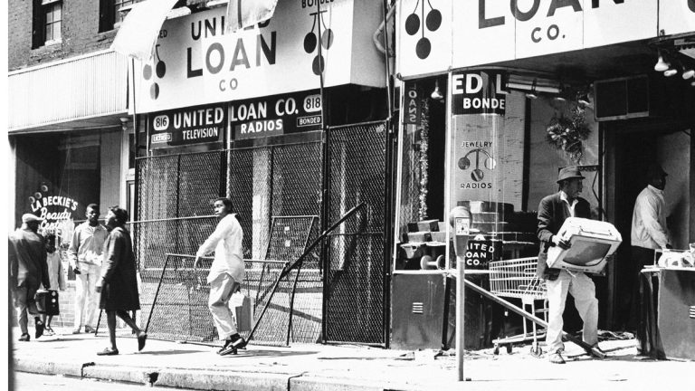 A man carts off a television set during looting incidents in Baltimore on Sunday, April 7, 1968. Many businesses were broken into, looted and burned that weekend. (AP Photo)