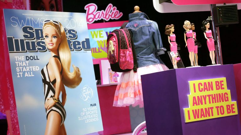 This Friday, Feb. 14, 2014, file photo shows a mock-up cover of Barbie on a 'Sports Illustrated' swimsuit issue at the Mattel booth at the American International Toy Fair in New York. A few weeks after her foray into the Sports Illustrated swimsuit edition, Barbie is entangled in controversy over her ties with the Girl Scouts. (AP Photo/Mark Lennihan)