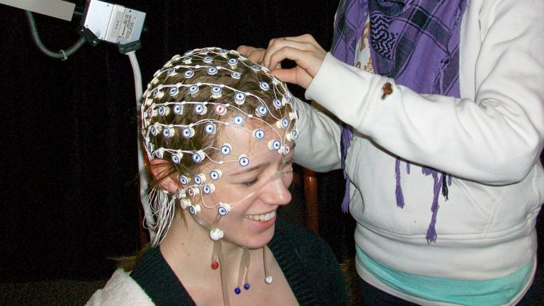 A researcher at McMaster University adjusts a net of electrodes on a participant's head. The device measures electroencephalography (EEG) responses within the brain