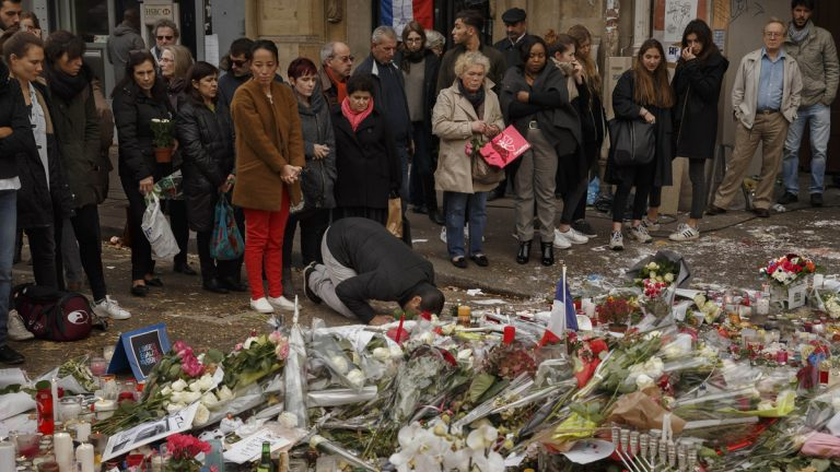A Muslim, center, prays in front of a floral tributes near the Bataclan concert hall after the terrorist attacks in Paris, Monday, Nov. 16, 2015.  France is urging its European partners to move swiftly to boost intelligence sharing, fight arms trafficking and terror financing, and strengthen border security in the wake of the Paris attacks. (AP Photo/Daniel Ochoa de Olza)