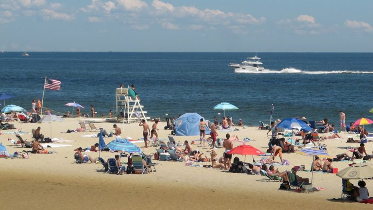 Beach-goers enjoy picture-perfect weather Thursday in Long Branch, New Jersey, where U.S. Rep. Frank Pallone and U.S. Sen. Bob Menendez urged federal lawmakers to reauthorize the Beach Act. (Phil Gregory/for WHYY))