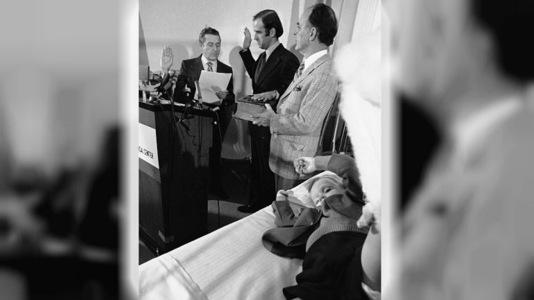 In this 1973 photo, four-year-old Beau Biden lies in a hospital bed as his dad is sworn in as the U.S. senator from Delaware. Beau was injured in an accident that killed his mother and sister in December 1972. (AP Photo/File)