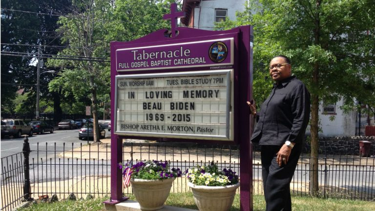 Bishop Aretha Morton stands beside the marquee at Tabernacle Full Gospel Baptist Cathedral in Wilmington. (Avi Wolfman-Arent, NewsWorks)