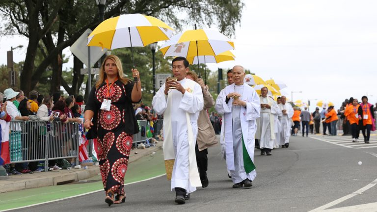 Priests helped Pope Francis administer Communion to thousands of Catholics who attended Mass on the Benjamin Franklin Parkway, Sunday, Sept. 27, 2015. (Lindsay Lazarski/WHYY)