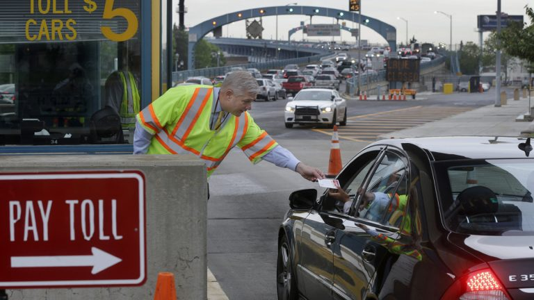 In May, Delaware River Port Authority CEO John Hanson, hands information cards to drivers in Camden at the toll lanes of the Benjamin Franklin Bridge between Camden and Philadelphia. The second phase of the PATCO train track replacement project over the bridge is set to begin this week. (AP Photo, file)