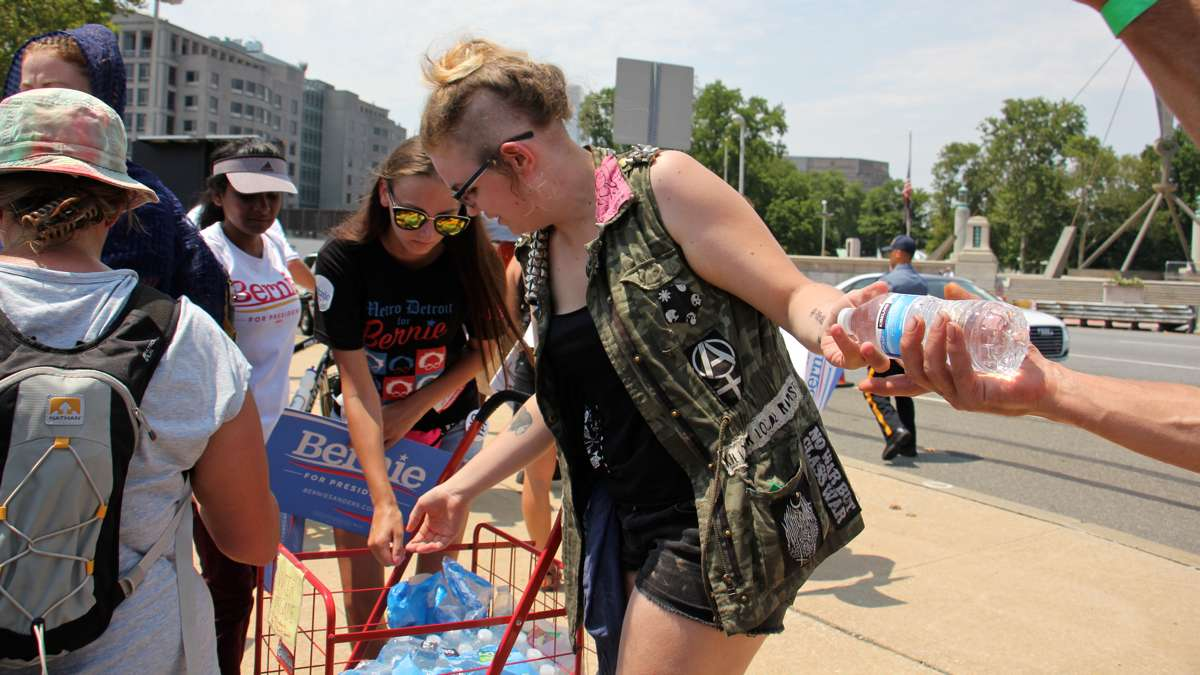 Volunteers hand out water bottles to thirsty marchers at the foot of the Ben Franklin Bridge. (Emma Lee/WHYY)