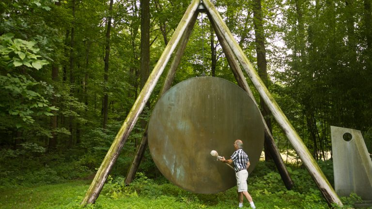 Harry Bertoia's son, Val, strikes a gong with a canvas-wrapped stick. The gong is one of Bertoia's sound sculptures at the family farmhouse in Berks County. (Charlie Kaier/WHYY)