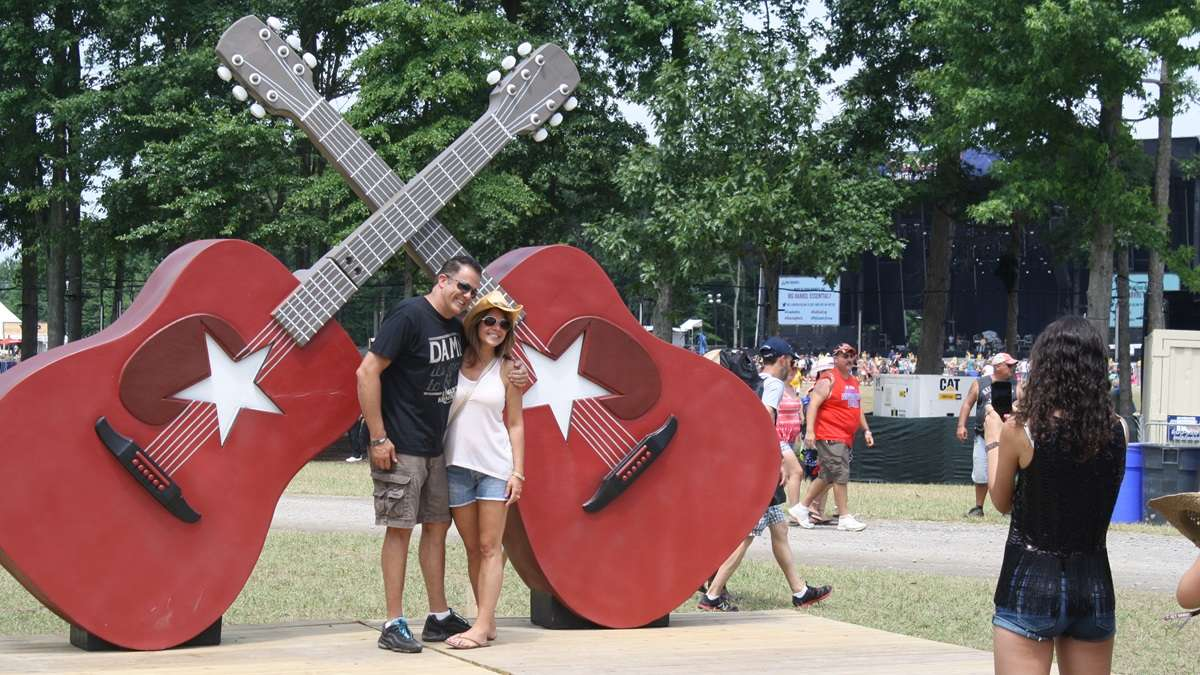 Country music fans pose for pictures in front of Big Barrel's signature crossed guitars. There will be no follow up to last year's inaugural festival. (Mark Eichmann/WHYY)