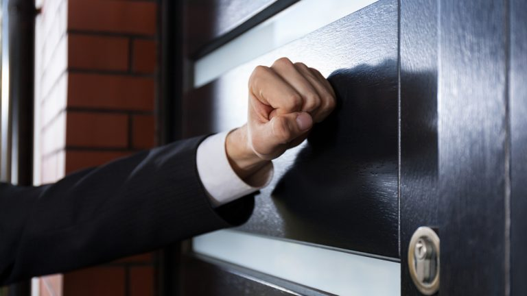 (<a href='http://www.bigstockphoto.com/image-74914648/stock-photo-hand-knocking-on-the-door'>Big Stock</a>)